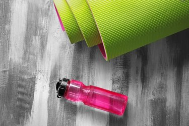 Yoga mat and bottle of water on wooden background for exercise to lower obesity risk