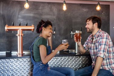 Couple talking and drinking beer in a bar
