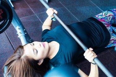 Asian girl lifting weights at the bench press