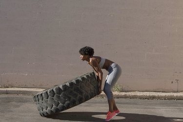 Woman lifting tire truck while exercising against wall