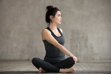 Young woman in Parivrtta Sukhasana pose