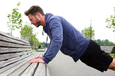 Handsome man doing pushup on bench