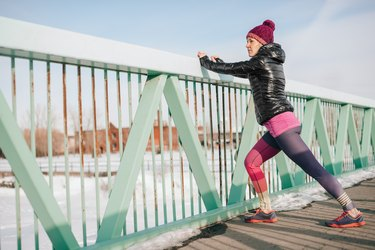Healthy caucasian woman keeping fit in the winter by stretching before jogging in a snow filled city