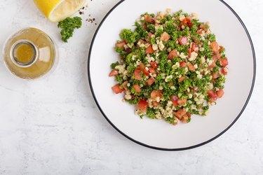Tabbouleh salad with bulgur, fresh herbs, vegetables and  salad  dressing