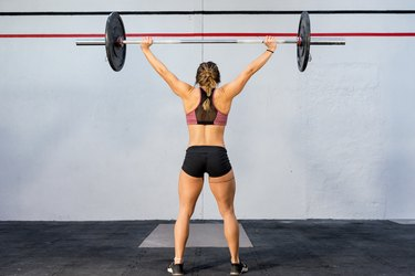 Woman doing overhead barbell press at the gym to strengthen her shoulders.