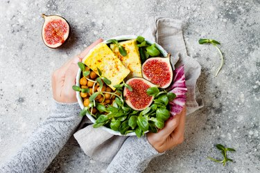 Vegan, detox Buddha bowl recipe with plant-based protein foods and turmeric roasted tofu, figs, chickpeas and greens. Top view, flat lay