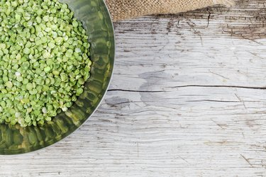Stainless steel bowl with uncooked green split peas.