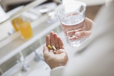 Woman taking vitamins and glass of water