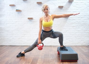 Woman doing kettlebell side lunges to build leg and butt muscles while burning belly fat