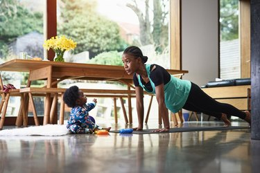 Baby boy assisting mother exercising