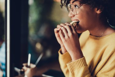 Side view of a woman eating a sandwich in a restaurant