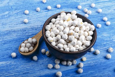 Dry chickpeas in a clay plate with a spoon on a blue wooden background.