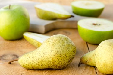 Fresh sweet green pears with apples, aka natural laxatives, on wooden table for foods for constipation