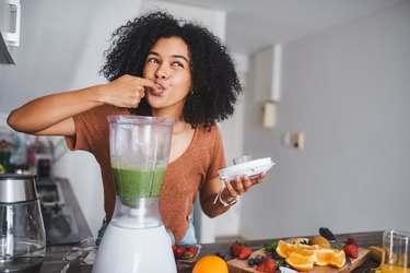 Woman tasting green smoothie from a blender in the kitchen
