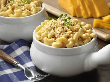 Macaroni and cheese in a white bowl on blue plaid tablecloth
