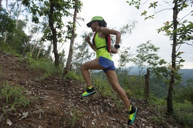 Sportswoman cross country ultra marathon trail runner running in rainforest