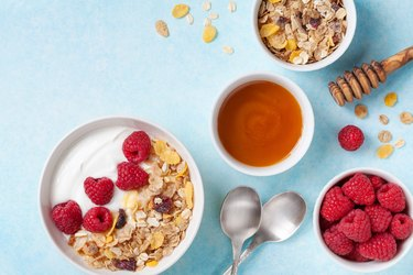 Greek yogurt in bowl with ingredients raspberries, honey and muesli on blue table top view.
