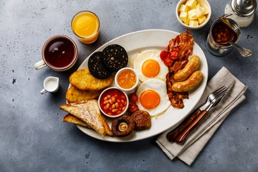 Full fry up English breakfast with fried eggs, sausages, bacon, black pudding, beans, toasts and tea