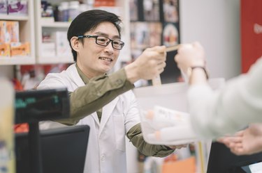 an asian chinese male  pharmacist taking over the shopping basket from his customer and smiling in pharmacy store