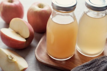 Apple cider vinegar with mother in glass bottles, probiotics food for gut health