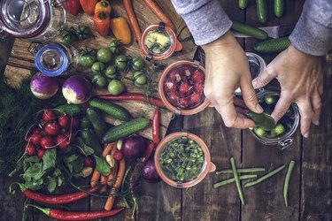 overhead shot of hands preserving vegetables like cucumbers and radishes in jars