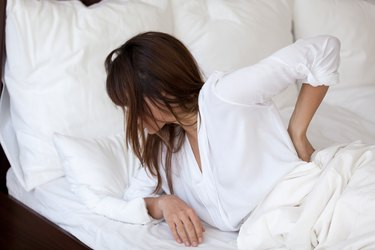 Tired woman suffering from back pain having bad sleep