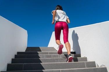 Stairs running woman doing run up on staircase - female runner