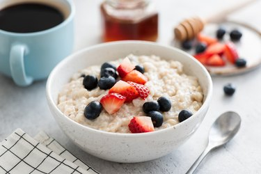 Oatmeal porridge with berries, honey and cup of coffee