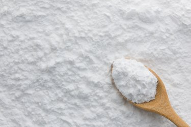 Close-up of tapioca starch or flour powder in wooden spoon on starch background