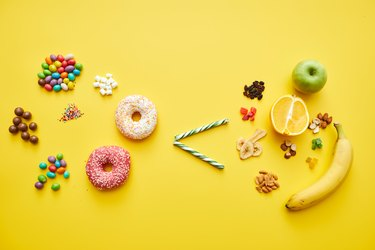 Choosing healthy sugar concept: sweets and baked food is less than fresh and dried fruits on bright yellow background
