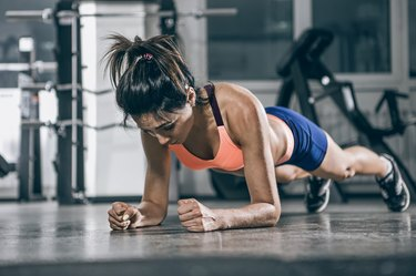Muscular woman on a plank position.
