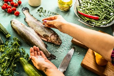 Female woman hands sprinkle with salt raw trout fishes for keto electrolytes