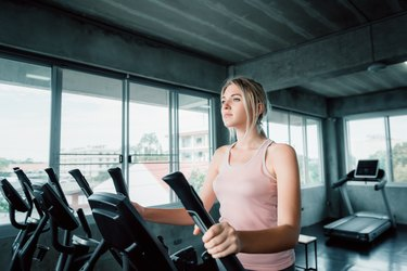 Portrait of Pretty Asian Woman is Workout in Fitness Gym., Attractive Woman is Working Out on Elliptical Machine Machine., Sport Club and Healthy Concept.