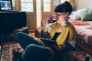 A happy woman drinking a glass of wine at home while using her tablet