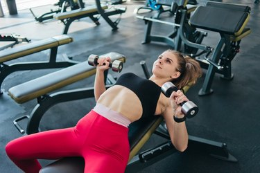 Fit young woman doing  dumbbell press lying down on inclined bench in gym