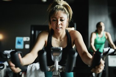 Portrait of woman riding indoor bike during class in cycling studio