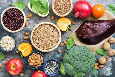 Foods high in iron. liver, broccoli, persimmon, apples, nuts, legumes, spinach, pomegranate. Top view, flat lay.