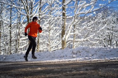 woman jogging on road through snowy winter rural landscape on sunny cold day