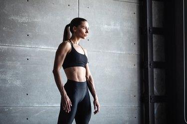 Sports woman portrait wearing black sportswear on dark wall background.