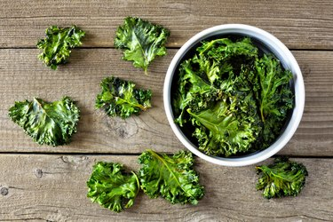 Bowl of healthy kale chips, top view on wood
