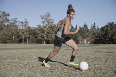Woman on football pitch playing football