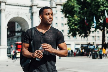 Afro-Caribbean guy in London with bottle of water practicing how to how to eat healthy on vacation