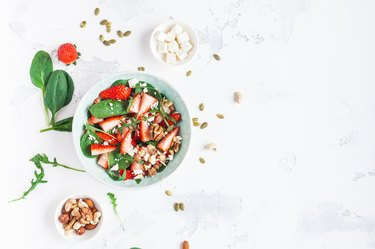 Spinach leaves, sliced strawberries, nuts, feta cheese on white background