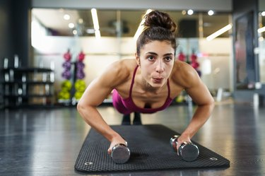 Woman doing push-ups exercise with dumbbell in a fitness workout