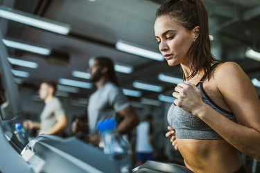 Determined female athlete jogging on treadmill in a gym.