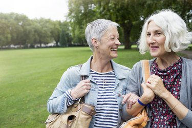 Two older women walking and laughing together in a park