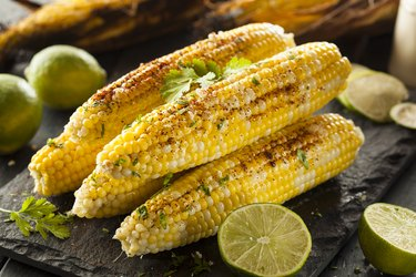Grilled Mexican-inspired corn on the cob with cut limes