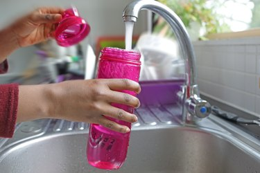 Detail of hands filling water bottle at a sink