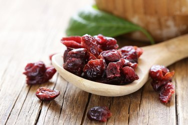 Dried cranberries in wooden spoon on a wooden table