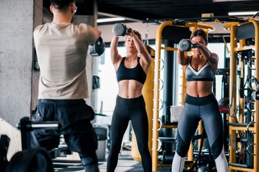 Trainer exercising with his clients at the gym.